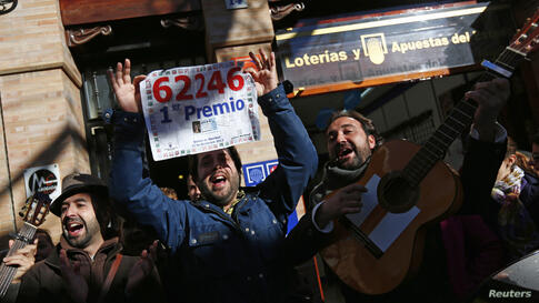 """People sing as they show a poster of the winning number to the first prize of Spain's Christmas Lottery """"El Gordo"""" (The Fat One) outside a lottery shop where the lottery number was sold in Sanlucar la Mayor, southern Spain."""