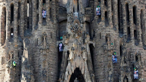 In this photo released by Greenpeace, protesters holding signs saying 'Liberty' in various languages hang from Sagrado Familia Basilica in Barcelona, Spain. The protesters are calling for the release of 28 Greenpeace activists, a Russian photographer a...