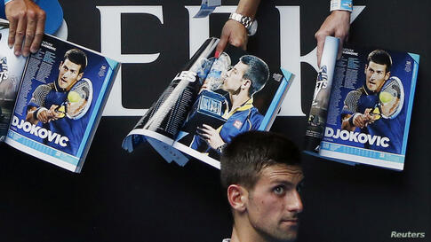 Novak Djokovic of Serbia walks past magazines featuring pictures of himself as he signs autographs after winning the men's singles match against Leonardo Mayer of Argentina at the Australian Open 2014 tennis tournament in Melbourne, Australia.