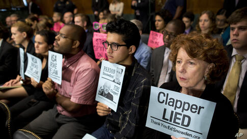 Protesters hold signs during a Senate Judiciary Committee oversight hearing on Capitol Hill in Washington, D.C., on the Foreign Intelligence Surveillance Act with National Security Agency Director Gen. Keith Alexander and National Security Agency Direc...