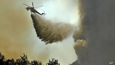 A helicopter drops a load of water above the High Park wildfire, about 15 miles west of Fort Collins, Colorado.