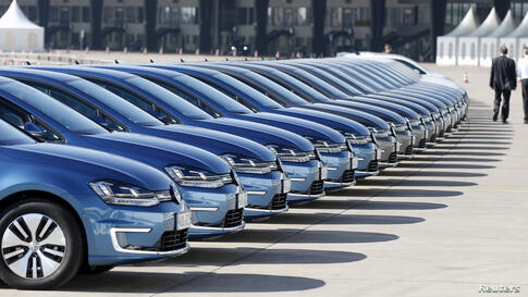People walk past a row of Volkswagen e-Golf cars during the company's annual news conference in Berlin, Germany.