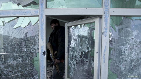 An Afghan policeman inspects a building used by insurgents after an operation near the Indian consulate in Mazar-i-Sharif. Afghan special forces killed a group of insurgents holed up in a house in the northern city of Mazar-i-Sharif, bringing to an end...