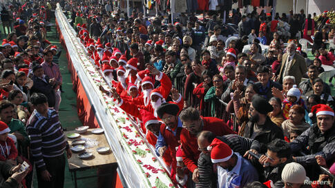 A man wearing a Santa hat (R) prepares to cut a cake that is 201-feet (61 meters) long as boys dressed in Santa Claus costumes cheer during Christmas celebrations in the northern Indian city of Chandigarh.