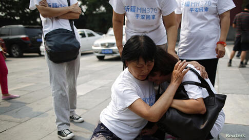 A family member of a passenger aboard the missing Malaysia Airlines flight MH370 comforts another relative as they gather to pray at Yonghegong Lama Temple in Beijing, China.