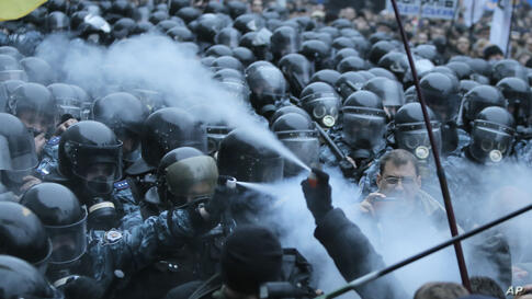 Opposition protesters and riot police spray tear gas against each other in front of the Ukrainian Cabinet of Ministers in Kyiv. Tens of thousands of demonstrators rallied in the center of Kyiv to demand that the government reverse course and sign a lan...