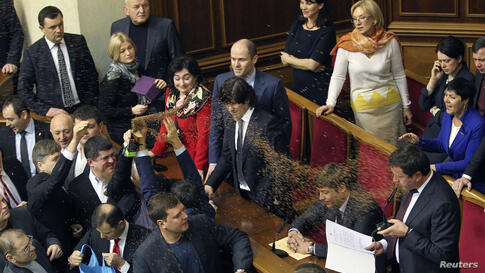 Opposition deputies throw buckwheat at newly elected deputy Viktor Pylypyshyn (R) as he takes the oath in Ukrainian Parliament in Kyiv. In Ukraine, buckwheat is a symbol of bribing voters.