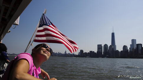 A woman rides a ferry on the harbor in New York City.