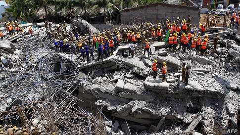 Indian rescue workers look for survivors in the rubble of a collapsed multi-storeyed building in Porur town, situated on the outskirts of Chennai. At least nine people were killed and dozens feared trapped after an 11-storey residential block crumbled,...