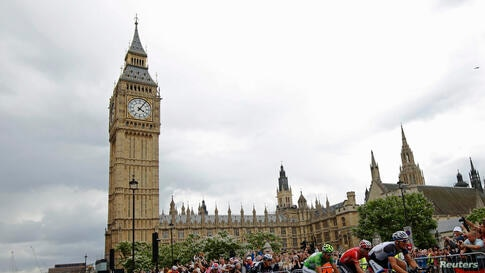 A pack of riders cycles passes the Big Ben clock tower and Houses of Parliament during the third 155 km stage of the Tour de France cycling race from Cambridge to London.