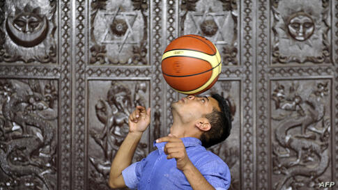 Thaneswar Guragai makes an attempt to break a Guinness World Record by keeping a basketball spinning on his nose for seven seconds, in Kathmandu, Nepal.