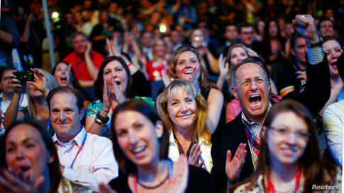 Delegates cheer as an image of Mitt Romney is displayed during the opening session, August 27, 2012.