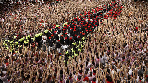 The band plays music after the launch of the 'Chupinazo' rocket, to celebrate the official opening of the 2014 San Fermin fiestas, in Pamplona, Spain.
