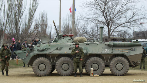 Military personnel stand next to an armored personnel carrier (APC) in the Crimean port city of Feodosiya, Ukraine, March 2, 2014.