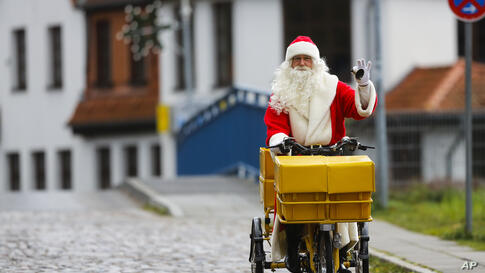 A man dressed as Santa Claus rings a bell as he arrives on a bike for the opening of the most famous German Christmas mail office in the small village of Himmelpfort (Heaven's Door) north of Berlin, Germany. Last year, over 292,000 children from all ov...