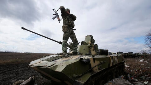 A Ukrainian soldier stands atop an armored vehicle at a military camp near the village of Michurino, Ukraine.