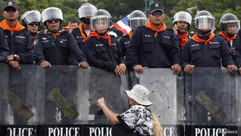 A woman takes pictures in front of a line of policemen blocking protesters against an amnesty bill, on the main road near the government and parliament buildings in central Bangkok, Thailand. The Thai Senate will likely reject an amnesty bill which cri...
