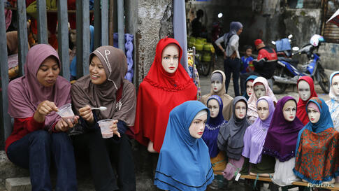 Girls sit near mannequins displaying hijabs for sale at Tanah Abang market, ahead of the holy fasting month of Ramadan, in Jakarta, Indonesia.