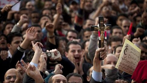 An anti-government protestor holds a Christian cross as others shout slogans during a demonstration at Tahrir Square in Cairo, Egypt, Wednesday, Feb. 9, 2011. Protesters appear to have settled in for a long standoff, turning Tahrir Square into a makeshift