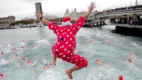 A participant in a colorful costume jumps into the water during the104th edition of the Copa Nadal (Christmas Cup) in Barcelona's Port Vell, Spain.