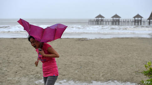 A woman walks on the beach of Qinglan port, as strong wind breaks her umbrella in Wenchang, south China's Hainan province.  China braced for a powerful super typhoon heading for its southern coast after the storm left a trail of destruction and at leas...