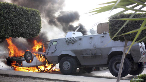 Protesters set a car on fire near a police vehicle during clashes with riot police at Nasr City district in Cairo, Eghpt.