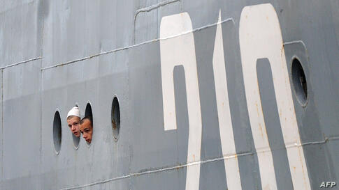 Russian sailors look through the porthole as they arrive aboard the Smolniy in Saint-Nazaire, western France.