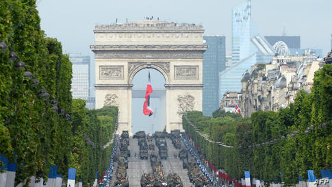 Armored vehicles drive down the Champs-Elysees avenue during the annual Bastille Day military parade in Paris, France.