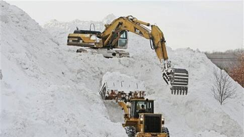 Workers use heavy equipment to create a mountain of snow collected from surrounding parking lots at Shoppers World in Framingham, Massachusets, USA, January 28, 2011.