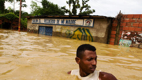A man walks in the flooded streets in Barlovento in the state of Miranda outside Caracas December 1.  (REUTERS/Miranda Government/Handout)