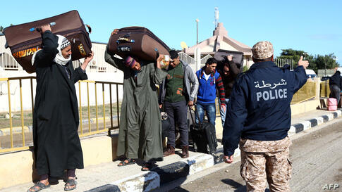 Egyptians walk carrying their belongings toward the Libyan side of the Ras Djir border crossing as they head to Tunisia for a flight evacuating them back to Cairo. Since the release of a gruesome video showing the beheading of Egyptian Christians by Is...