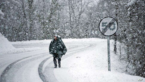 Antonio Lazza, a 60 year old pilgrim from Italy, walks alongside the road of Saint James's Way during a snow fall on a Spring morning near the Pyrenees town of Erro, northern Spain. The Saint James Way is a pilgrimage route ending in Santiago de Compos...