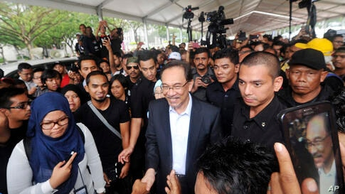 Malaysian opposition leader Anwar Ibrahim, center, is greeted by supporters as he leaves the court house after the first day of his final hearing in Putrajaya, Malaysia, Tuesday, Oct. 28, 2014.  Malaysia's top court on Tuesday began hearing a final appeal