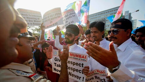 Police stop a group of the students from the National Students Union of India, during a protest outside the U.S. consulate in Mumbai. India's information minister lashed out at the United States on Friday and demanded an apology for the treatment and a...