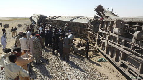 Officials, rescue workers and residents gather near the passenger train derailed after it was hit by a bomb attack in Dera Murad Jamali, located in the Nasirabad District of Balochistan province, Pakistan.