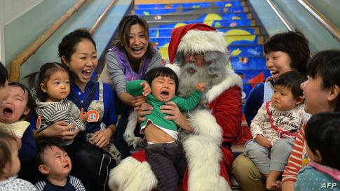 A man playing Santa Claus from Finland sits with children at the Hinomoto nursery school in Tokyo, Japan.