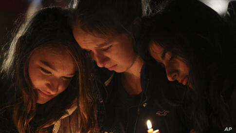 Kate Suba, left, Jaden Albrecht, center, and Simran Chand pay their respects at one of the makeshift memorials in honor of the victims of the Sandy Hook Elementary School shooting, Sunday, December 16, 2012, in Newtown, Connecticut.
