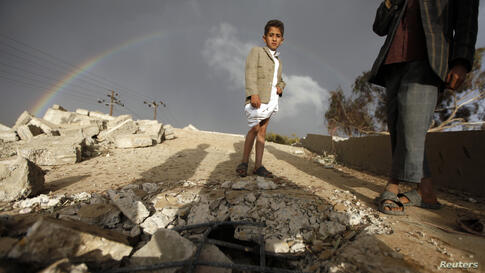 A boy stands on the ruins of his school which was bombed by militants of the Shi'ite al-Houthi group during recent conflicts against local tribes in the Hamdan area west of the Yemeni capital Sanaa, March 23, 2014.