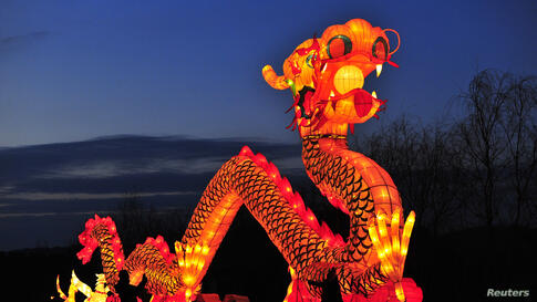 Tourists take a picture in front of a giant dragon lantern during a lantern festival in Shenyang, Liaoning Province, China.