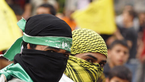 Palestinians wearing Hamas (L) and Fatah masks celebrate the reconciliation agreement between rival Palestinian factions Fatah and Hamas in a street in Gaza City May 4, 2011. Palestinian leaders formally ended a four-year rift between secular Fatah and th