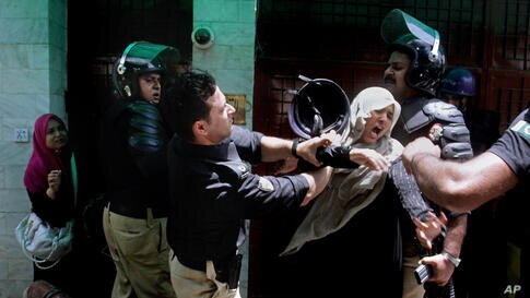 A police officer scuffles with a protester during clashes in Lahore, Pakistan. Police clashed with followers of an anti-Taliban cleric critical of the government in the eastern city, leaving at least seven people killed, officials said.