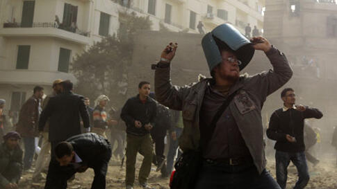 An opposition demonstrator throws a rock during clashes with supporters of President Hosni Mubarak Thursday near Tahrir Square in Cairo