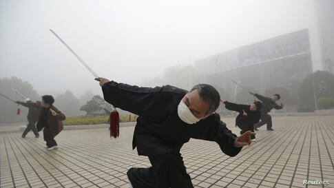 A man wearing a mask exercises on a hazy morning in Fuyang, Anhui province, China.