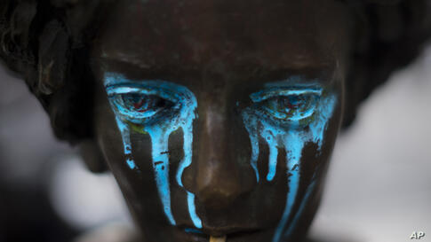Blue paint falls from the eyes of a vandalized statue, in Madrid,Spain.