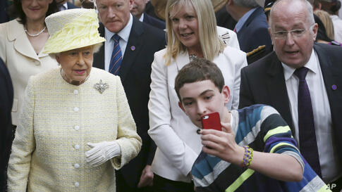 A local youth takes a selfie in front of Queen Elizabeth II during a visit to St. George's indoor market on in Belfast, Northern Ireland.