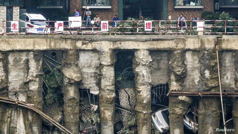 Cars are seen in a sunken open-air parking lot after heavy rainfall hit Chengdu, Sichuan province, China. Four cars fell into the pit and one was left stuck on the edge of a railing as the ground sunk, according to local media.