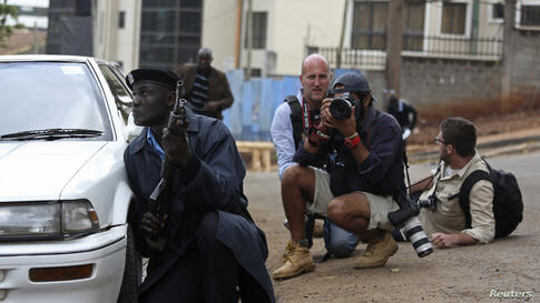 A policeman and photographers take cover after hearing gun shots near the Westgate shopping centre in Nairobi, Sept. 23, 2013.