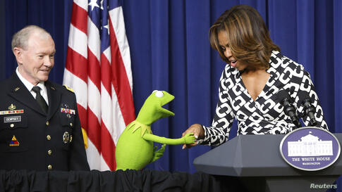 """U.S. First Lady Michelle Obama greets Kermit the Frog as Chairman of the Joint Chiefs of Staff U.S. Army General Martin Dempsey introduces a showing of the new movie """"Muppets Most Wanted"""" at the White House in Washington, Mar. 12, 2014."""