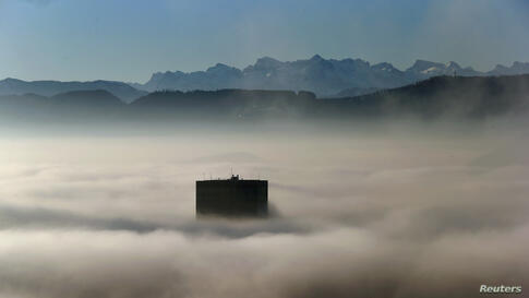 The top of Switzerland's highest skyscaper the Prime Tower (126 meters/413 ft) peeps through the fog in front of the Swiss Alps, early morning in Zurich.