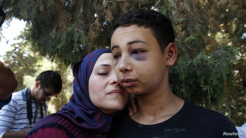 Tariq Khdeir (R) is greeted by his mother after being released from jail in Jerusalem. An Israeli judge released the 15-year-old American of Palestinian descent from jail and placed under house arrest. Khdeir was detained and beaten by Israeli police i...
